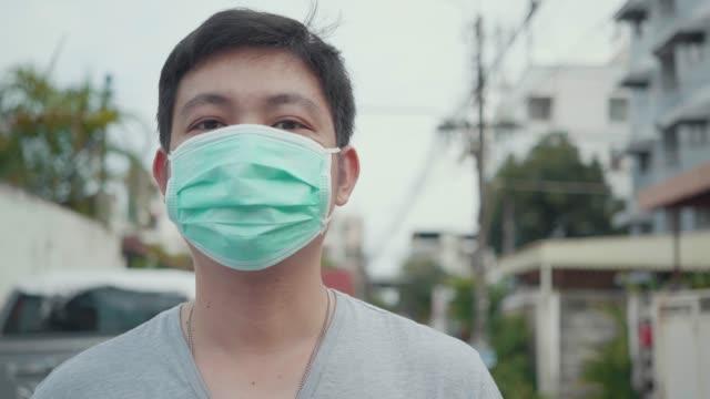 vídeos de stock e filmes b-roll de close up asian young man wearing a face mask. - covid hair