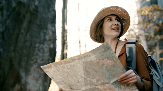 Close up Attractive young woman in stylish hat and a tourist map in her hands looking around Close up Attractive young woman in stylish hat and a tourist map in her hands looking around. Round dolly shot navigational compass stock videos & royalty-free footage