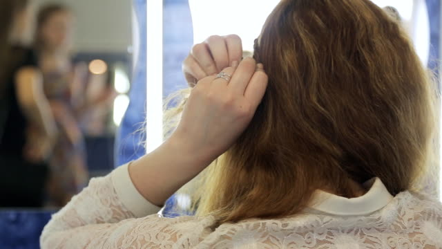 Close up back view of female making hair in model school video