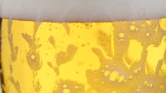 Close up background of pouring lager beer in glass