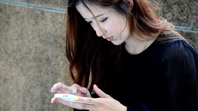 クローズアップ美しい若い女性のスマートフォンを使用して、 - 学生生活点の映像素材/bロール