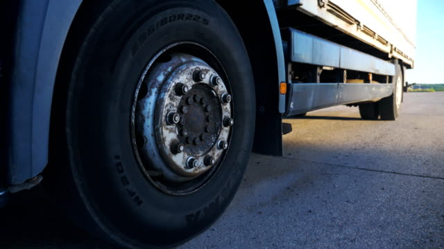 close up big wheel of truck riding on asphalt road through countryside. lorry speeding along highway riding to destination. big truck goods at evening time. transport and logistic concept. slow motion - truck tire video stock e b–roll