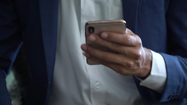 vidéos et rushes de gros plan business people à l'aide de téléphone intelligent avec shopping - interview