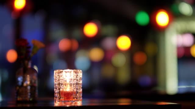 chiudere la luce della candela e fiorire sul tavolo. sfondo luci colorate sfocalizzato. - soft focus video stock e b–roll
