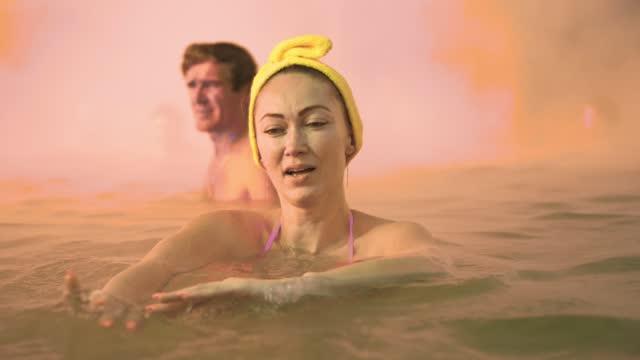 부드러운 매직 핑크 조명 증기와 야외 전통 스파에서 뜨거운 식염수 목욕에서 수영에 백인 여성을 닫습니다. 지열 스파. - 스파 온천 스톡 비디오 및 b-롤 화면