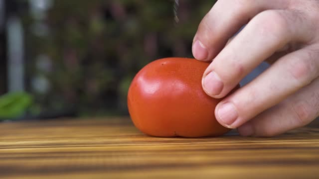 vídeos de stock e filmes b-roll de close up chef cook cutting fresh tomato in half on wooden board. male hand with knife cutting tomato on kitchen. vegetable ingredient, vegetarian diet. healthy food and fitness menu. cooking concept - sauce tomatoes