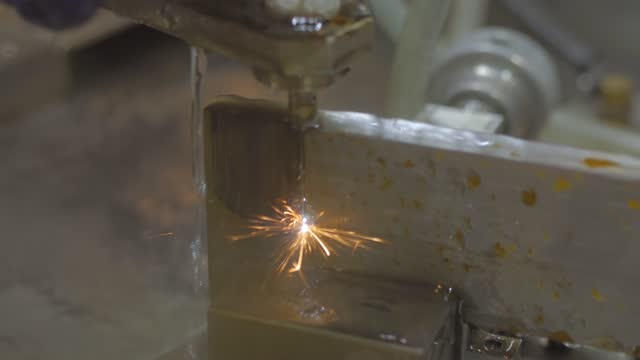 Close up: cnc wire cutting machine working with metal workpiece with sparks