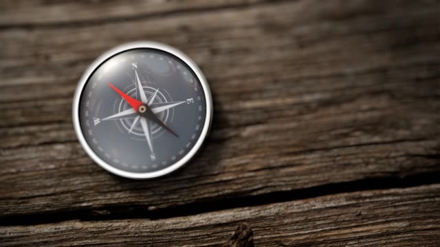 Close up compass showing north on a wooden table. Compass with a needle pointing North on a wooden table. Close up view. Objective concept. 3D Rendering navigational compass stock videos & royalty-free footage