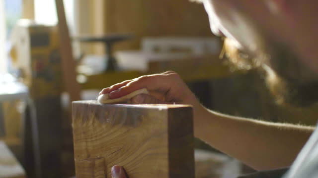 close up concentrated carpenter woodworker rubs lacquer in wooden plank in backlight video