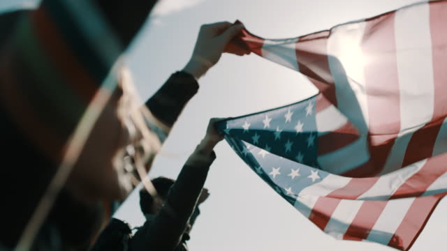 Close up, couple of hikers raising american flag up in the air
