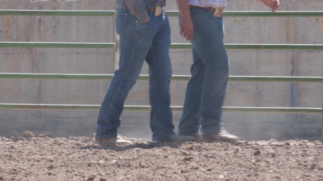 Close up cowboy boots to faces as two men walk in the dry dust ground rodeo stadium