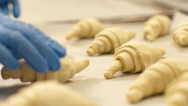 vidéos et rushes de bouchent croissant couché sur papier dans le bac avant la cuisson dans la boutique confiserie - boulanger