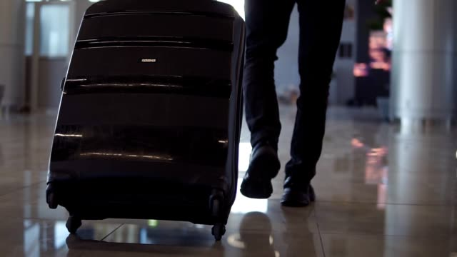 Close up, cropped shot of man legs with the black baggage walking to the airport terminal. Slow motion. Rare view video