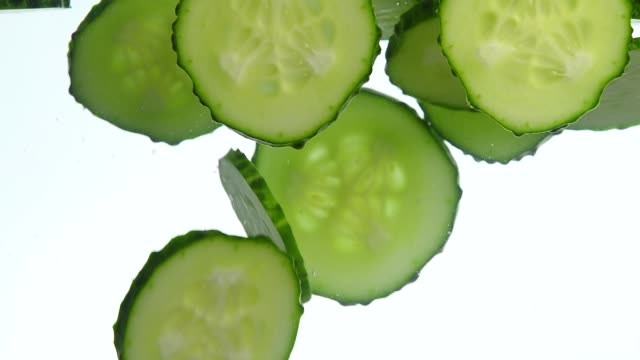 close up cucumber slices thrown floating in water - cetriolo video stock e b–roll