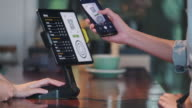 istock close up customer use mobile phone pay contactless with tablet at counter bar in cafe.small business start up.customer service concept 1192477422