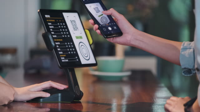 close up customer use mobile phone pay contactless with tablet at counter bar in cafe.small business start up.customer service concept - digital mobile consumption video stock e b–roll