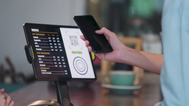 close up customer use mobile phone pay contactless with tablet at counter bar in cafe.small business start up.customer service concept - stand video stock e b–roll