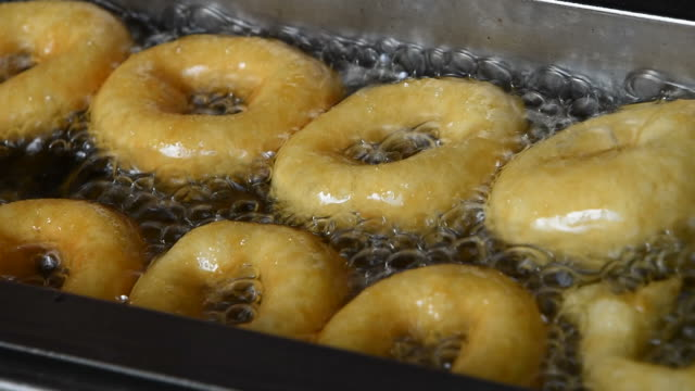 Close up deep frying ring donuts in oil video