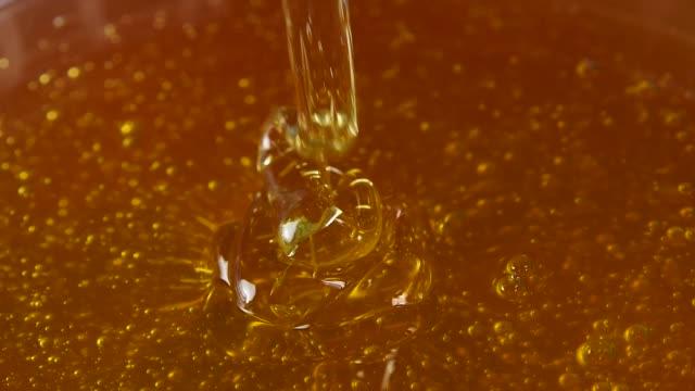 vídeos y material grabado en eventos de stock de cierre la cuchara de metal en un tazón de miel - pegajoso