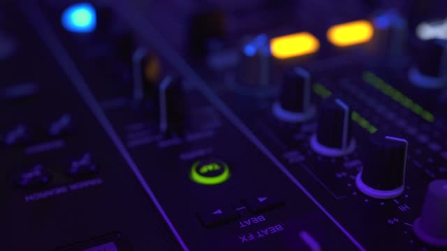 vídeos de stock e filmes b-roll de close up dj mixer player and sound console for house music party. dj controller for mixing music and colorful light in nightclub. disc jockey panel and mixing deck at dance party - ibiza
