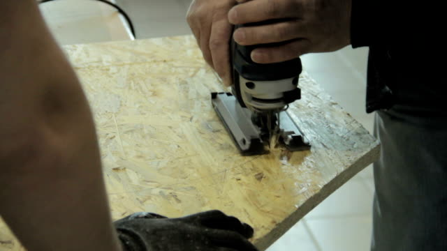 Close up electric jigsaw cutting a piece of wood video
