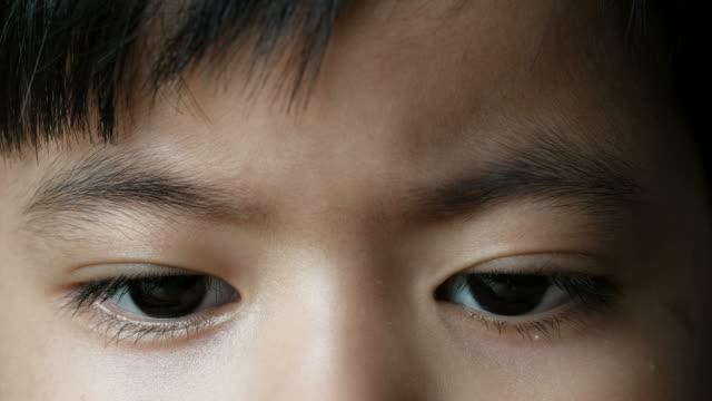 Close up eye of little  boy reading a book video
