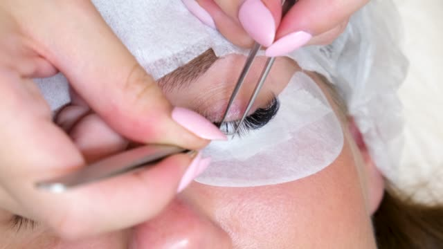 Close up eyelash extension Procedure. Eyelash extension beautician glues long artificial eyelashes to the woman client in beauty salon. 4k footage Close up eyelash extension Procedure. Eyelash extension beautician glues long artificial eyelashes to the woman client in beauty salon. 4k footage. eyelash stock videos & royalty-free footage