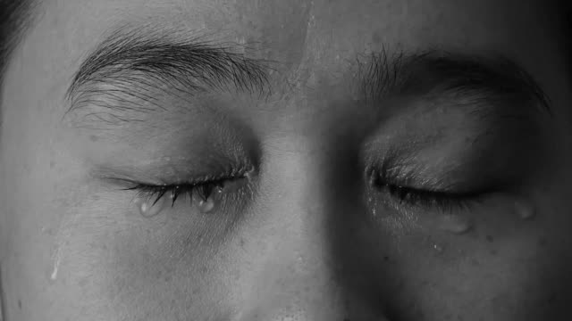 close up eyes of woman crying with tear on black background. - strillare video stock e b–roll