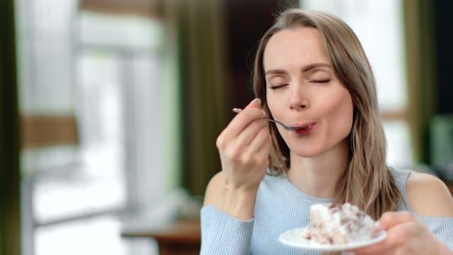 特寫面可愛的女人吃開胃蛋糕用勺子感覺愉快。4k 龍紅色相機 - 烤酥皮糕點類 個影片檔及 b 捲影像