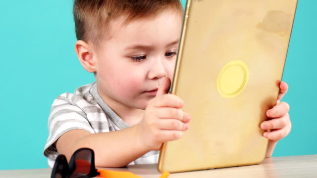 close up face cute little child uses a tablet pc sitting at table, isolated on blue - solo neonati maschi video stock e b–roll