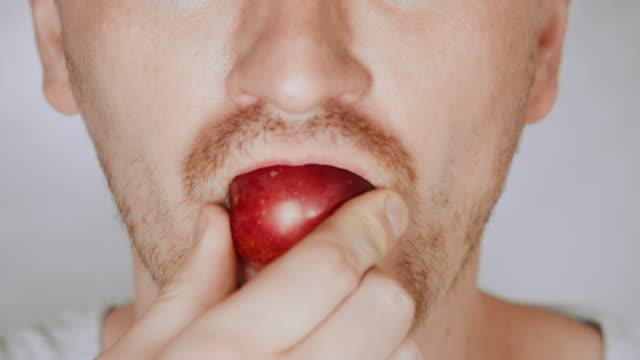 close up face fair man eat plum details lower face blond male eating plum caucasian person portrait plum stock videos & royalty-free footage