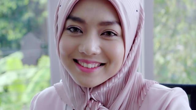 vidéos et rushes de fermez-vous vers le haut du visage d'une jeune femme musulmane de beaux yeux utilisant la couleur noire traditionnelle de foulard de hijab sourit avec la caméra regardant de rire - indonésie