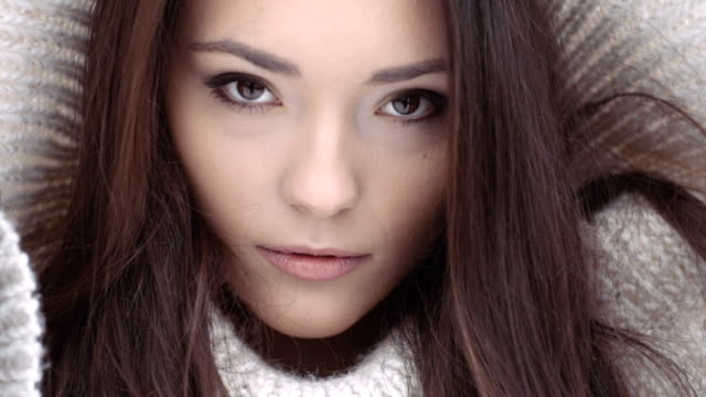 Close up face of beautiful natural young brunette woman in winter scenery. video