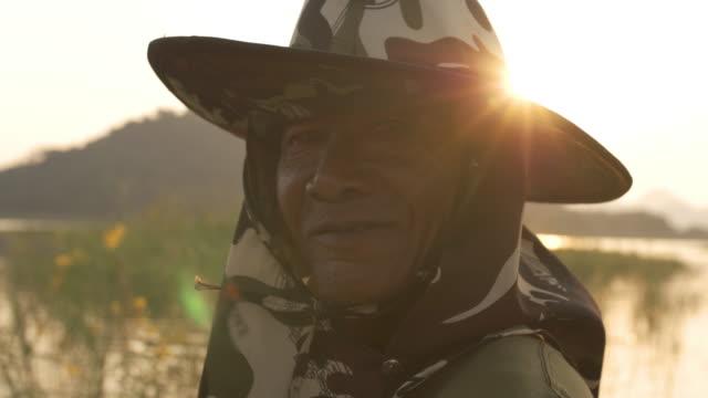 漁師の顔をクローズアップ。夕方に笑顔のアジアの老人 - 漁師 外人点の映像素材/bロール