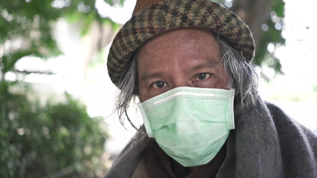 CU Close up Face of homeless man senior man looking at the camera CU Close up Face of homeless man senior man with protective face mask look up camera during covid-19 corona virus pandemic. homelessness stock videos & royalty-free footage