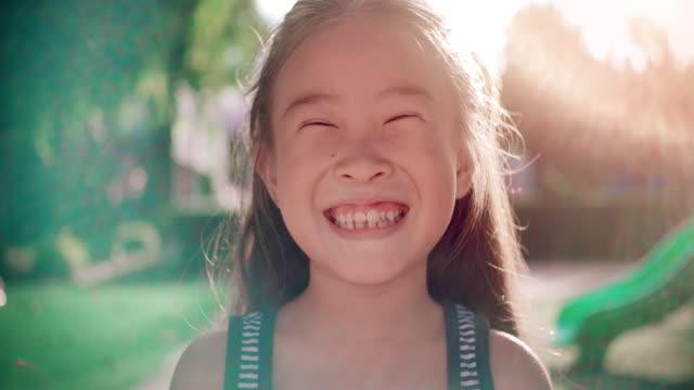 slo mo 클로즈업 얼굴 의 미소 행복한 아시아 소녀 - 아시아인 스톡 비디오 및 b-롤 화면