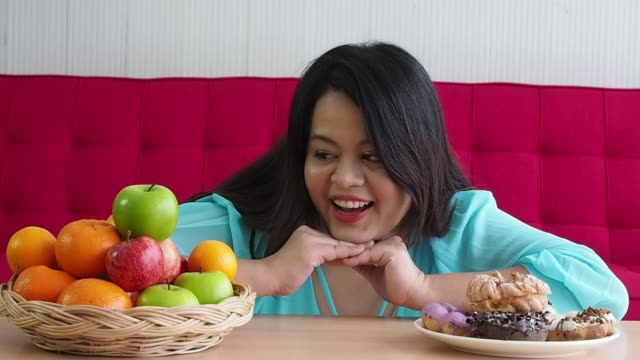 close up face plus size women choosing healthy food fruits and donuts