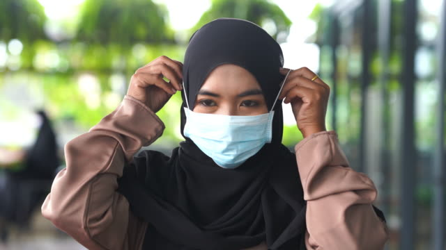 Close Up Face Young Asian Muslim Woman with  surgical mask protection - vídeo
