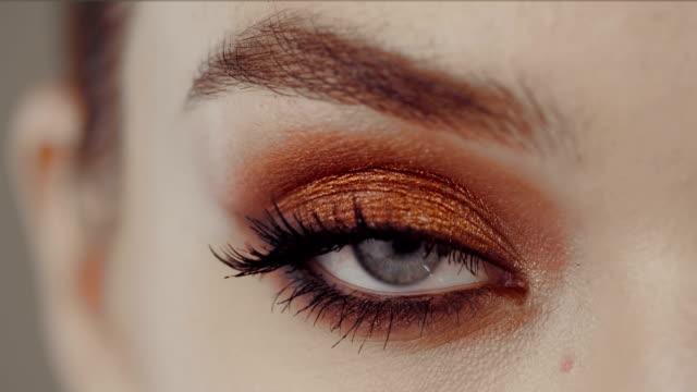 vidéos et rushes de fermez-vous vers le haut de l'œil féminin avec le maquillage lumineux vers le haut. - fard à paupières