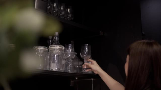 Close up female hands selecting and picked three empty glass bottles from drawer in the kitchen