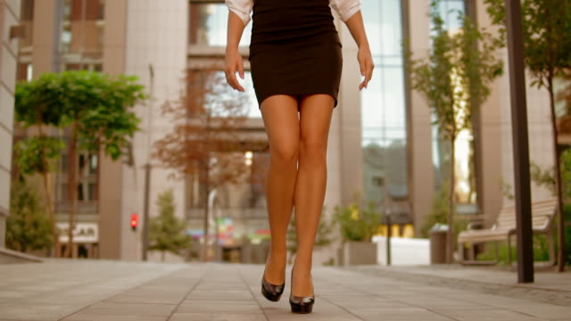 vídeos de stock e filmes b-roll de close up female legs walks in business area of town - saia