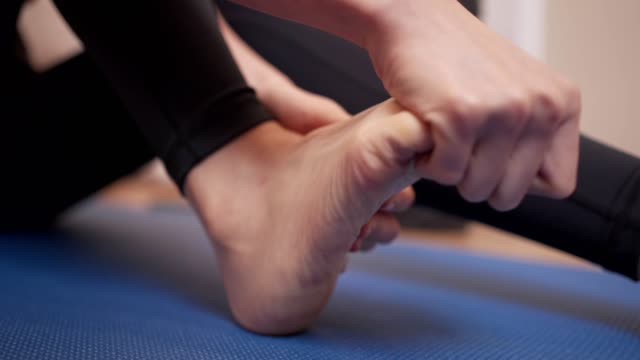 vídeos de stock e filmes b-roll de close up female massaging her foot, ankle sprain pain, bone and joint problem, sit down on the floor yoga mat, hand on feet toe, flexible, female sit down on exercise mat, sport injury concept - músculo humano