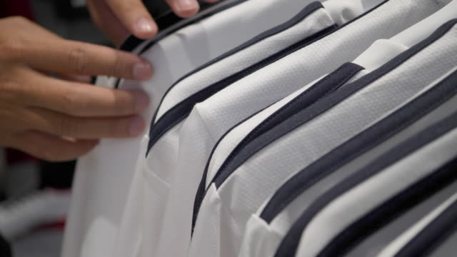 Close up finger of male customer select white T-shirts in a shop video