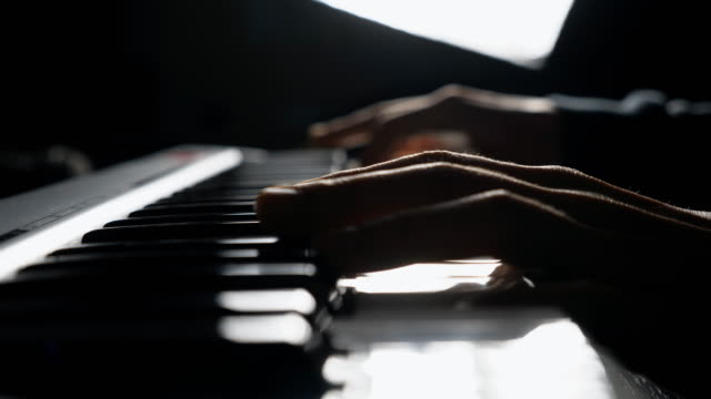 Close up fingers of pianist pressing at the synthesizer keys.  Hands of man plays solo of music. Arms of male musician playing at synthesizer. Slow motion Side view Isolated shot