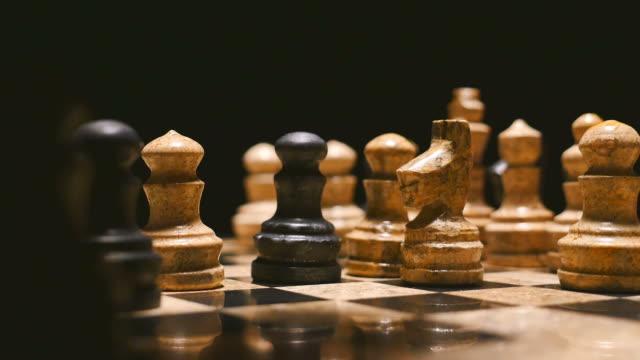 aufnahmen von einem schachspiel auf einem schwarzen hintergrund hautnah - könig schachfigur stock-videos und b-roll-filmmaterial