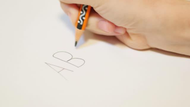 Fechar a filmagem de uma mão child´s com um lápis escrevendo ABC em um papel branco - vídeo