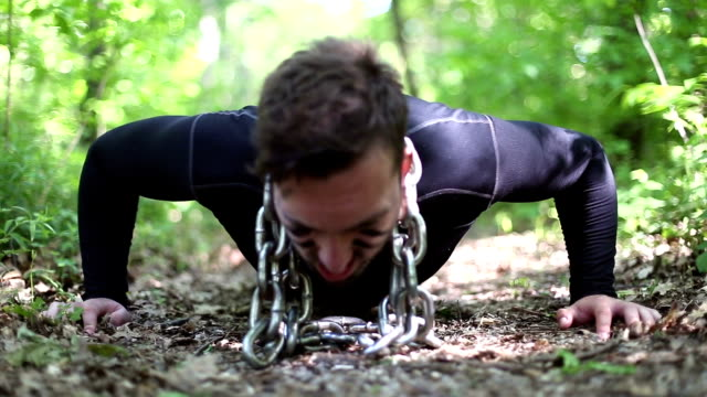Close up footage of a man doing push ups with chains around his neck video