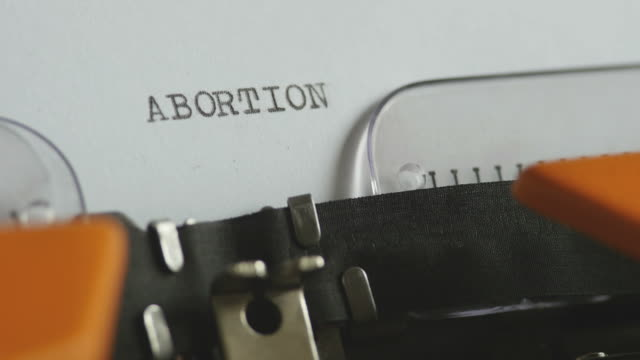 Close up footage of a person writing ABORTION on an old typewriter, with sound video