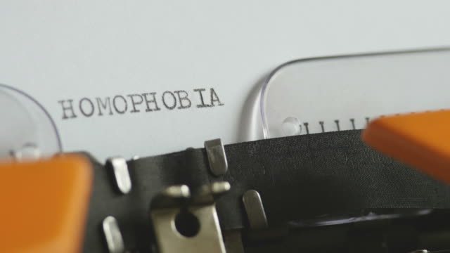 Close up footage of a person writing HOMOPHOBIA on an old typewriter, with sound