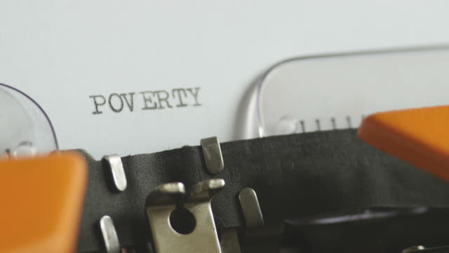 Close up footage of a person writing POVERTY on an old typewriter, with sound - video